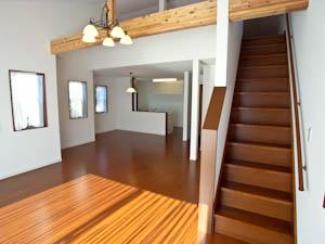 キッチンに向かって段々状に広がっていくユニークなリビング。脇にはロフトへの階段が。