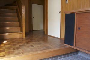 玄関まわりは木目調で、靴箱の黒が効いている。