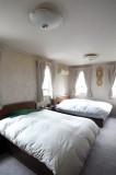 ダブルベッドを2台置いても余裕の広さ、の寝室。