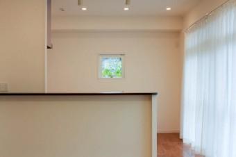 キッチンのカウンター越しに見える、額装のような小窓。